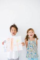 描いた絵を持つ男の子と女の子