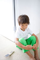 床に座り膝を抱える男の子と携帯電話