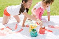 芝生の上でペンキで絵を描く子供二人