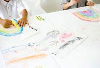 クレヨンで絵を描く子供の手元