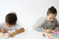 机に向かい絵を描く子供二人