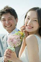 一緒にブーケを持つ笑顔の花嫁と花婿