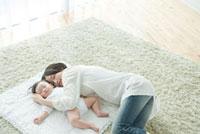 カーペットの上で一緒にお昼寝をする母親と赤ちゃん