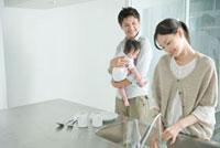 キッチンでグラスを洗う母親と赤ちゃんを抱える父親