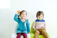 並んで椅子に座る少女と少年