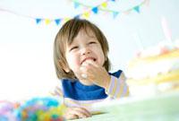 ケーキを前にテーブルにつく笑顔の少年