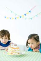 テーブルの上のケーキを見つめる少年と少女