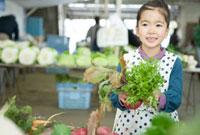 市場の野菜を手に取る女の子