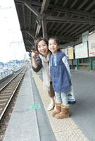 駅のホームで電車を待つ祖母と孫娘
