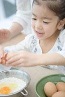 玉子を割る6歳の女の子 10161001465| 写真素材・ストックフォト・画像・イラスト素材|アマナイメージズ