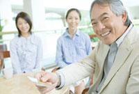 カードで支払いを依頼する父と後ろで微笑む母と娘