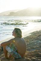 海岸に座る若い男性