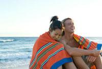 海岸に座る若いカップル