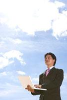 空の下でパソコンをするビジネスマン