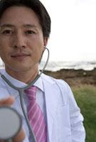 聴診器を当てる30代の医師