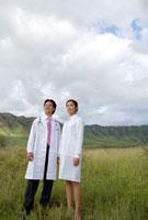 山並みや野原の前に立つ男女二人の医療関係者