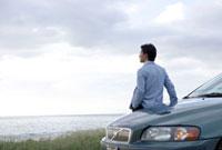 車を降りて海を眺める30代男性の後姿