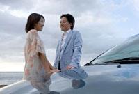 車の横で会話をするカップル
