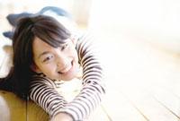 床に寝転びくつろぐ笑顔の10代女性 10161001976  写真素材・ストックフォト・画像・イラスト素材 アマナイメージズ