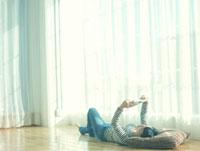 部屋で仰向けになり本を読む10代女性 10161001992  写真素材・ストックフォト・画像・イラスト素材 アマナイメージズ