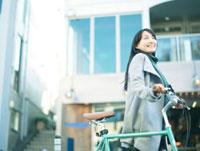 自転車を押して歩く10代女性
