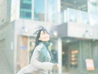 街中を笑顔で走る10代女性