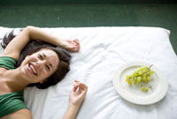横たわる笑顔の女性とブドウ