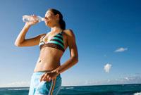 海岸で水を飲む女性