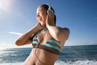 海岸で音楽を聴く女性