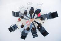テーブルを囲んで手を重ねるビジネスマンたち