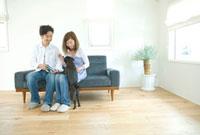 ソファで愛犬とくつろぐ男女
