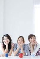 頬杖をつき考える20代女性3人