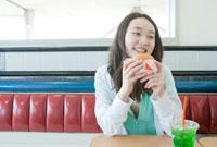 店内でハンバーガーを食べる10代の女の子