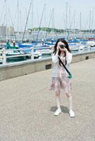 港湾でカメラを構える10代の女の子