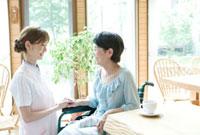 向かい合う20代の介護士と60代の女性 10161004076| 写真素材・ストックフォト・画像・イラスト素材|アマナイメージズ