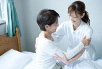 介護士から介護を受ける60代の女性
