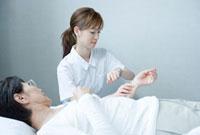 脈を測る20代の介護士