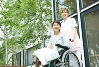 車いすを押す20代の女性介護士と60代の要介護者