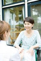 笑顔で向き合う20代の女性介護士と60代の要介護者