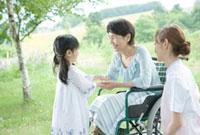 孫の手を握る60代の女性と見守る女性介護士