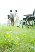 孫と散歩をする60代女性と女性介護士の後姿