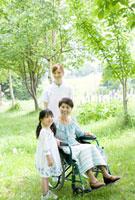 孫と散歩をする60代女性と女性介護士