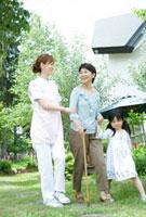 孫と手をつなぎ散歩をする60代女性と支える女性介護士