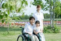 孫と寄り添う車いすの60代女性と女性介護士