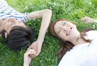 野原に寝転び手をつなぐ若いカップル
