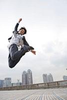 体を反らせて高くジャンプするビジネスマン
