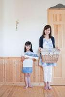 畳んだ洗濯物を持つ母と娘