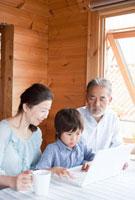 ノートパソコンに向かう孫息子と祖父母