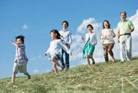 丘を歩く三世代家族