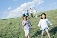 丘を駆ける孫と三世代家族